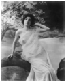 Young woman in gauzy dress posed seated on log c 1903.png