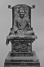 Frontal view of a cross-legged seated statue placed on a throne. His right arm rests on his leg, the left arm is bend and slightly raised.