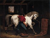 Oil painting of a horse groom, with his back to the viewer, brushing a large, white horse that is pawing the ground and turning to look at the groom.