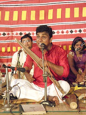 Folk process - A singer accompanies himself with an onavillu, amplified with microphones. Traditional folk music is transmitted in performance; as such, it adapts to audience tastes and available technologies.