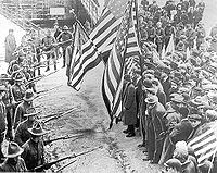 Example 2: Labor strikers of the Industrial Workers of the World holding American flags, held back by a militia bearing rifles and bayonets.