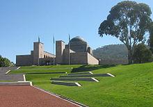 Вид на ухоженный холм;  ступеньки ведут ко входу в большое здание с куполом и тремя флагштоками впереди.