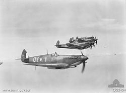 Five single-engined World War II-era monoplanes flying parallel to one another