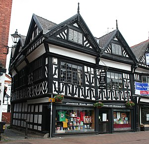 A black-and-white building in a corner position, with two gables to the front and three to the side.