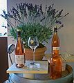 Image of wine bottles on a table with a plant in the background.