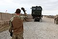 A British soldier, foreground, with Combat Support Logistics Regiment 12 ground-guides a U.S. Marine with Transportation Support Company, Combat Logistics Regiment 2 while offloading a heavy equipment vehicle 130225-M-KS710-166.jpg