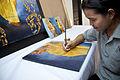 A craftswoman lacquering at Artisans Angkor.jpg