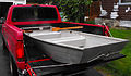 A small jon boat (johnboat) in a red pickup truck.jpg