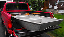 small modern jon boat in the bed of a pickup truck.