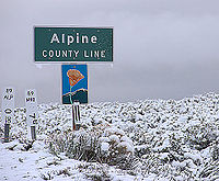 A road sign denoting the Alpine County line along California State Route 89 during a snowstorm in May 2008.