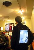 Back view showing the man facing away. Here we see the backwards facing video display on the jacket.