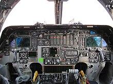 Una cabina de vuelo, dominada por una mezcla de instrumentos nuevos y analógicos.  En ambos lados hay yugos de control.  La luz entra por las ventanas delanteras