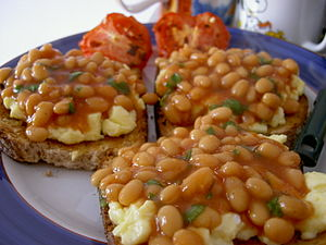 A dish of baked beans over scrambled eggs on t...