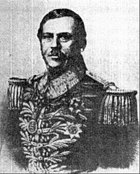 Lithographic half-length portrait of a man with dark hair and mustache who is wearing an elaborately heavily embroidered military tunic bedecked with medals across the chest and heavy epaulets