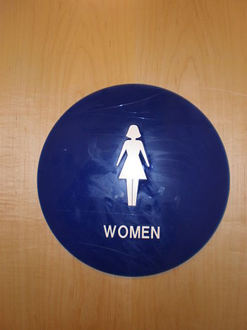 A plastic female restroom sign in an office bu...