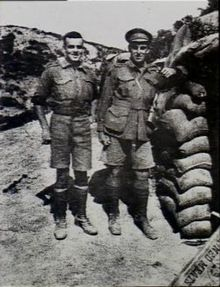 Two men in military uniform standing side-by-side. The man on the left is slightly shorter and stockier, while the man on the right has his arm leaning on a stacked up pile of sandbags.