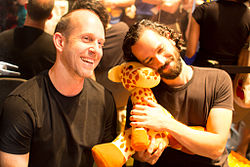 A man with short brown hair, sitting next to a man with curly black hair hugging a plush giraffe, both smiling at something to the right of the camera.
