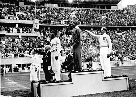 Jesse Owens on the podium after winning the long jump at the 1936 Summer Olympics Bundesarchiv Bild 183-G00630, Sommerolympiade, Siegerehrung Weitsprung.jpg