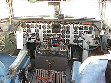 DC-7 cockpit viewed inside, facing forward. Three vertical pillars support a windscreen with two panes. Forty round instrument dials are on a flat panel in front of two seats. Facing each seat is a short column topped with a semi-circular control yoke. Between the seats are two clusters of engine throttles, one set of four for each pilot.