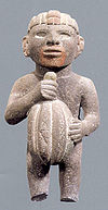 Aztec statuary of a male figure holding a cacao pod