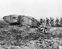 A group of soldiers with guns march on uneven ground past a wrecked tank and the body of another soldier