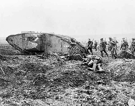 Files of soldiers with rifles slung follow close behind a tank, there is a dead body in the foreground