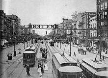 "New Orleans in the 1900s. ""Canal Street--The Broadway of New Orleans"". Shows view looking riverwards from the 800 block, with electric streetcar, pedestrian, and carriage traffic. Signage for streetcars to West End over center of neutral ground."