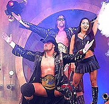 An Asian female with dark hair standing next to two male wrestlers wearing wrestling gear, black coats, and championship belts.