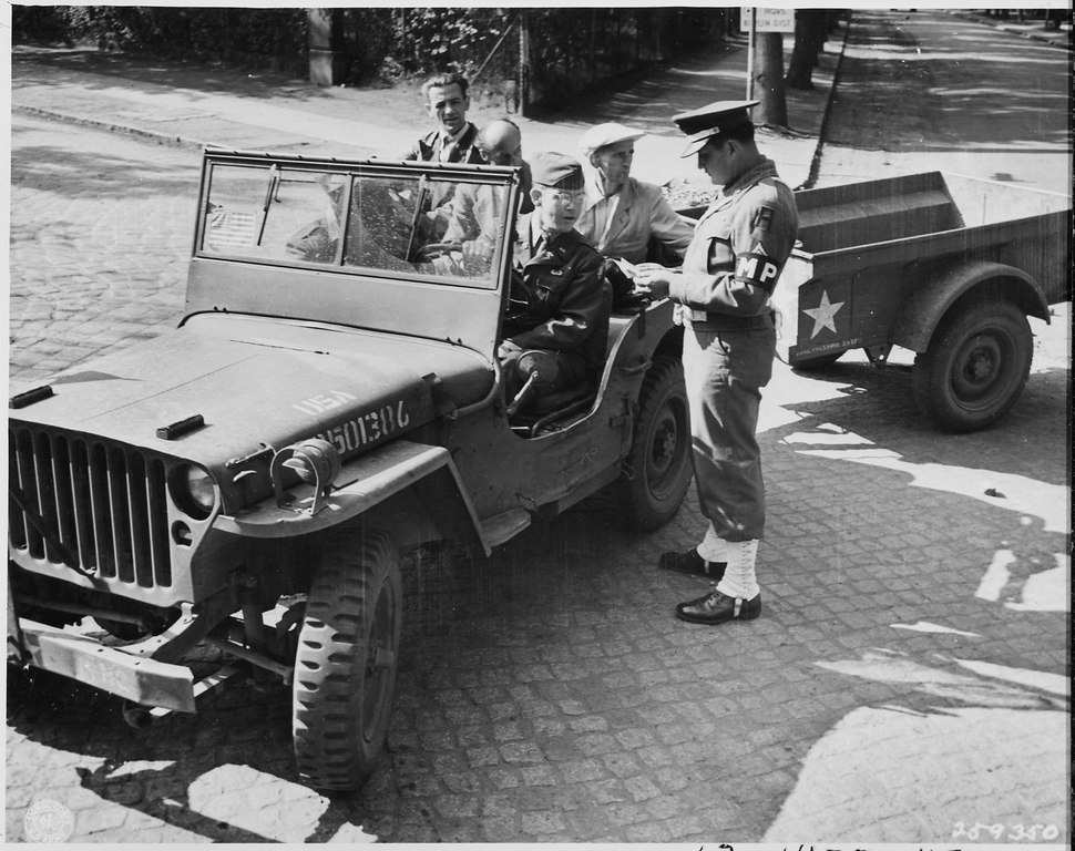Civilian Photo Technicians (in back of jeep) working for Counter Intelligence Corps, are accounted for by Captain... - NARA - 198977