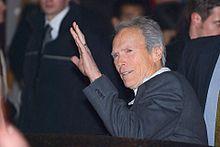 Photographie de Clint Eastwood saluant le public après une conférence de presse. Il est vêtu d'un costume gris foncé