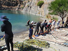 A group of about 12 divers on the shore of a flooded quarry preparing surface supplied diving equipment for diver training exercises. Several umbilicals are laid out for use in figure 8 coils.
