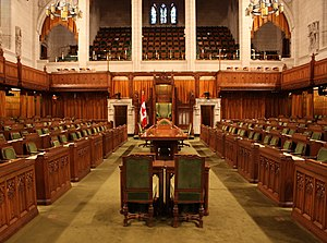 House of Commons of Canada - The chamber of the House of Commons; the Speaker's chair is at the rear and centre in the room.