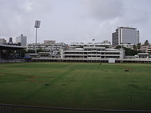 Brabourne Stadium in Mumbai. Image shows the playing field, part of west stand and the art-deco pavilion. Floodlight tower stands next to pavilion on the left.