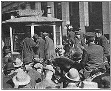 A crowd of men swarm around a streetcar and mounted police officers