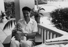David Bushnell is seated on a porch and holding a baby.