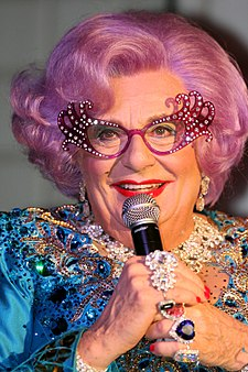 closeup of Dame Edna wearing sparkly blue dress, over-the-top eyeglass frames, and multiple finger rings