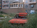 Destroyed red car in a abandoned zone nearnear amin eslami garden- Nishapur 6.JPG
