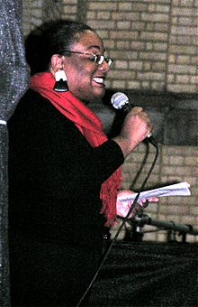 50ish woman in black, with a bright red scarf, large black-and-white earrings and glasses, smiling and holding a microphone in one hand and a sheet of paper in the other
