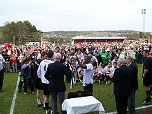 Two men in white football shirts and black shorts receive a silver trophy from an elderly man in a dark blazer.  More players look on, as do several more men in blazers and a crowd of spectators of all ages.  Several photographers are taking pictures of the presentation.