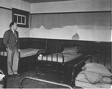 A black and white image of Dr. Le Vann in the Michener Centre, before a number of empty patient beds.