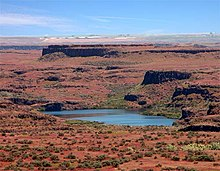 Reddish-brown terrain and many small green bushes surround a lake. Truncated ridges of dark rock run across the terrain parallel to the horizon and to each other beneath a blue sky.