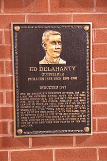 "A bronze-and-black metal plaque hung on a brick wall displays an engraving of a man's face; the main caption of the engraving reads ""Ed Delahanty; outfielder; Phillies 1888–1889, 1891–1901"