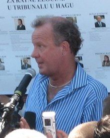 Ed wearing a blue and white striped shirt, speaking into a microphone