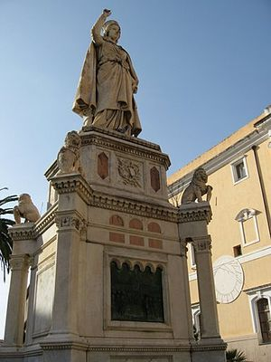Oristano - Oristano: Statue of Eleanor of Arborea, holding the Carta de Logu in her hand, with the sundial on the wall of the City Hall in the backdrop.