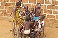 Enfants jouant Sékou (Bénin) en se transportant à l'aide d'une charrette à deux roues appelé Pousse-pousse au Bénin.jpg