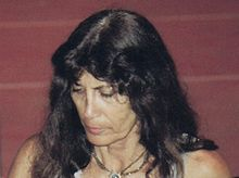 A white woman about 60 years old, black hair with eyes on ground.