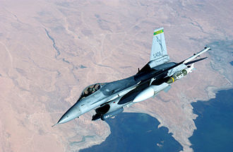 Joint Direct Attack Munition - JDAMs loaded under the left wing of a F-16 Fighting Falcon with a LITENING II Targeting Pod visible beneath the fuselage