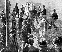 A cricketer leading his team off the field watched by a crowd