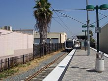A train station at ground level with a track on the left side. A light rail train is stopped at the station. Various buildings are located to the left of the station.