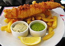 Fried fish on a pile of fried potato, with ramekins of tartar sauce and mushy peas.